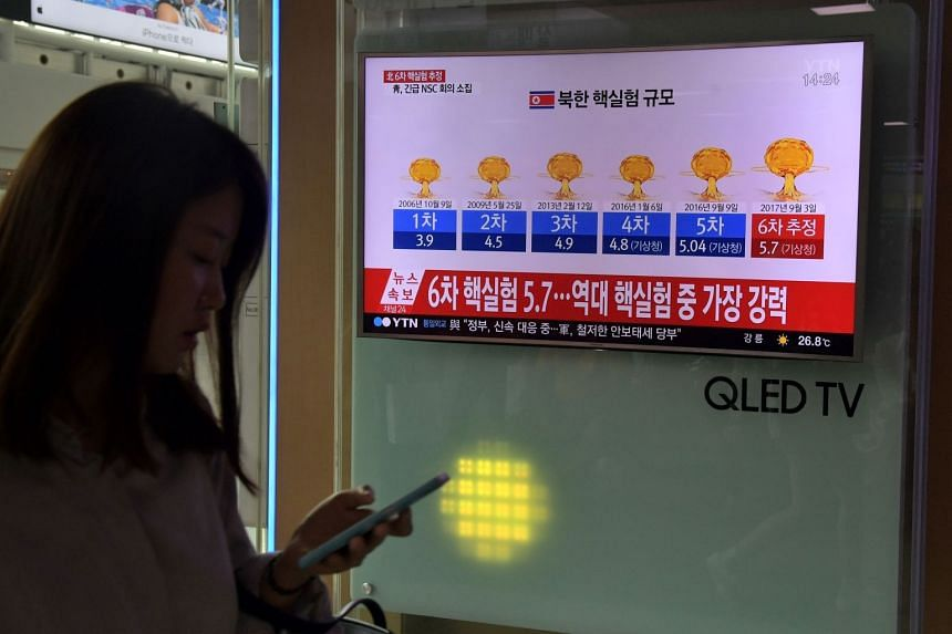 A woman walks past a television display at a train station in Seoul, on Sept 3, 2017, showing a news broadcast with a graphic about a history of North Korean nuclear tests.