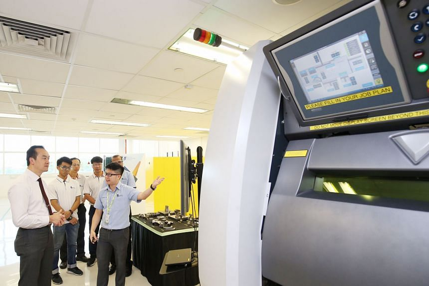 At A*Star's new Industrial Additive Manufacturing Facility yesterday, Dr Koh Poh Koon is shown a laser beam powder bed machine, which uses a laser beam to melt metal powder and turn it into 3D printing material. Technical components can then be produ