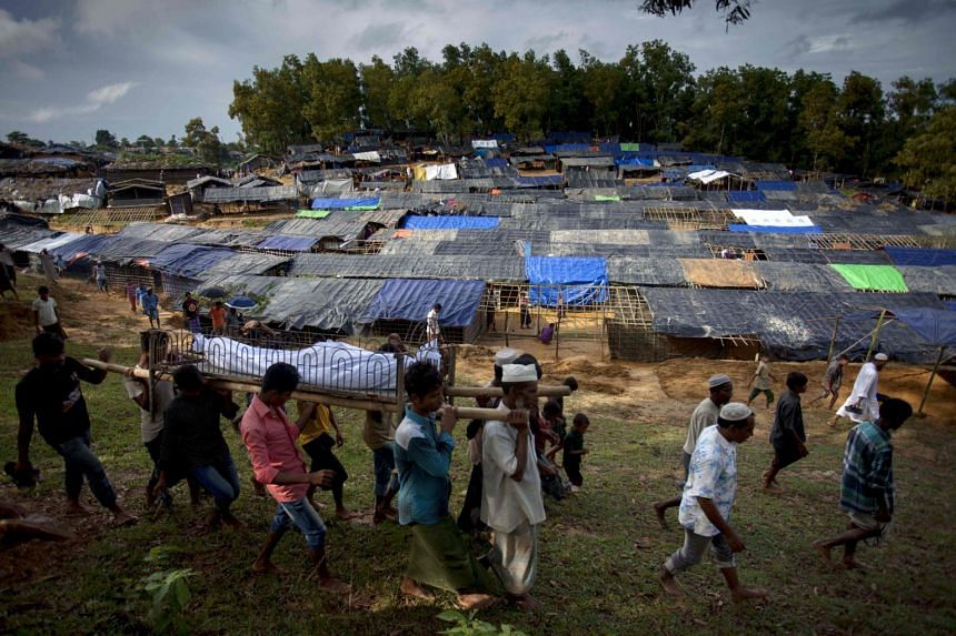 Rohingya Muslim men carry the body of 68-year-old man Asad Ali, who was allegedly shot by Myanmar's army while crossing the Naf river, at the Kutupalong Rohingya refugee camp in the Bangladeshi district of Ukhia on Sept 8, 2017.
