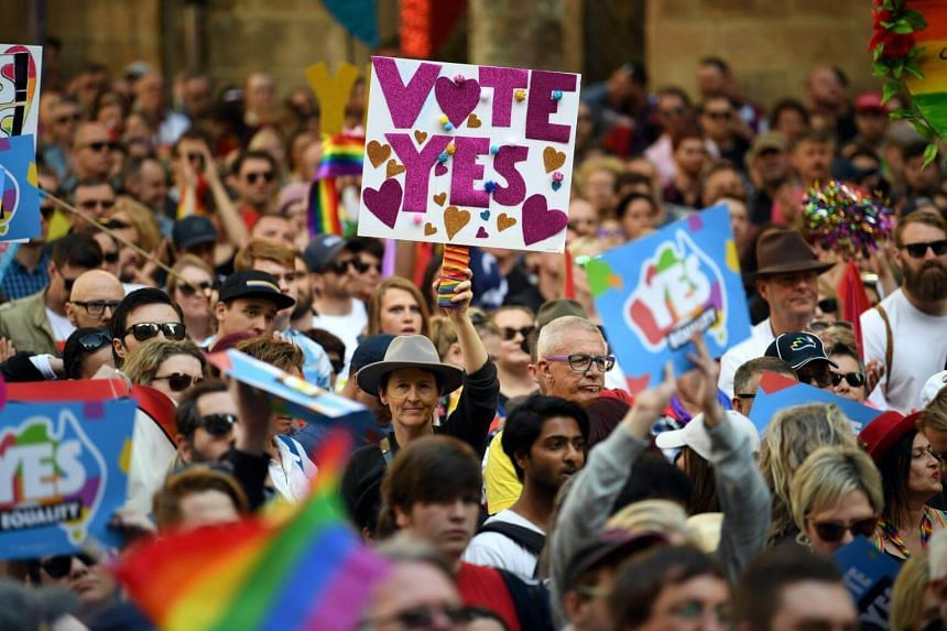 Supporters hold placards as they attend a same-sex marriage rally in Sydney, on Sept 10, 2017.