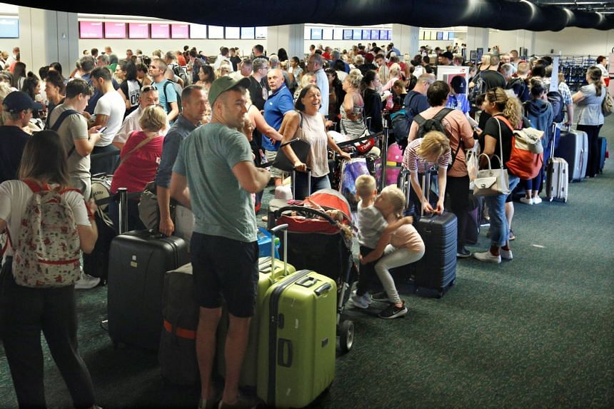 Departing passengers form a long queue to check in at Orlando International Airport in Florida.