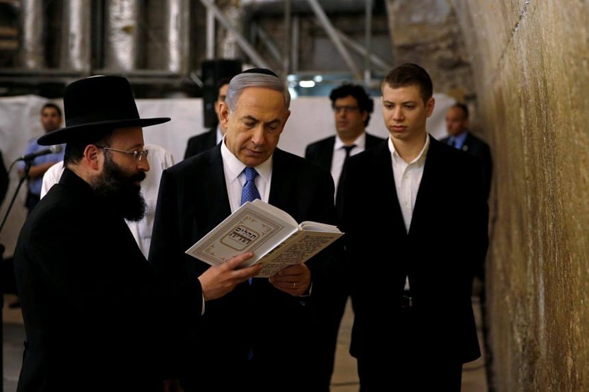 Israel's Prime Minister Benjamin Netanyahu (centre) reads a prayer with Western Wall Rabbi Shmuel Rabinowitz (left) as his son Yair (right) stands next to him, at the Western Wall, Judaism's holiest prayer site, in Jerusalem's Old City on March 18, 2