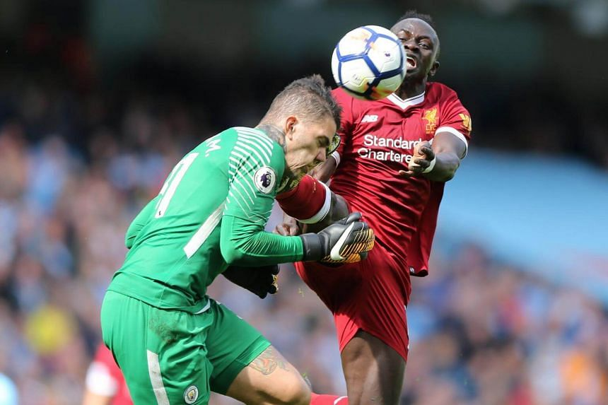 Manchester City's goalkeeper Ederson Santana de Moraes (left) is fouled by Liverpool's Sadio Mane during the English Premier League soccer match at the Etihad Stadium in Manchester, on Sept 9, 2017.
