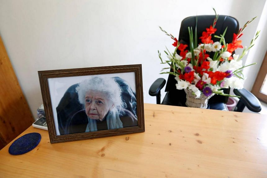 A photograph of late Nancy Hatch Dupree, an American historian, and a bouquet of flowers are seen in her office after she passed away, in Afghanistan Centre at Kabul University (ACKU), in Kabul, on Sept 10, 2017.