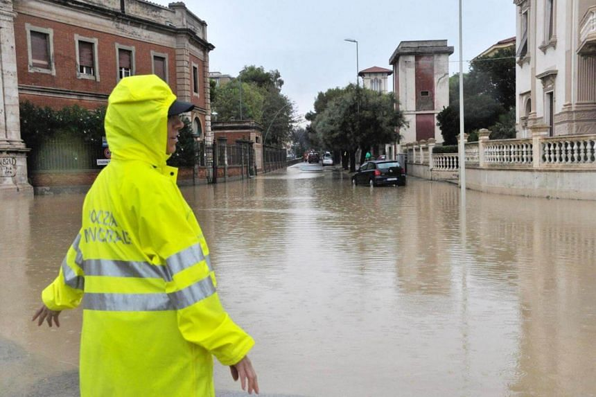 A police officer stands in a flooded crossing in Livorno, Italy, on Sept 10, 2017.