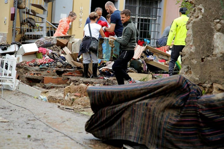 People are seen next to a damaged house, following floods in Livorno, Italy, on Sept 10, 2017.