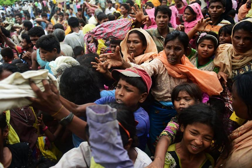 Newly arrived Rohingya refugees scuffle for relief supplies at Kutupalong refugee camp in the Bangladeshi locality of Ukhia, on Sept 9, 2017.