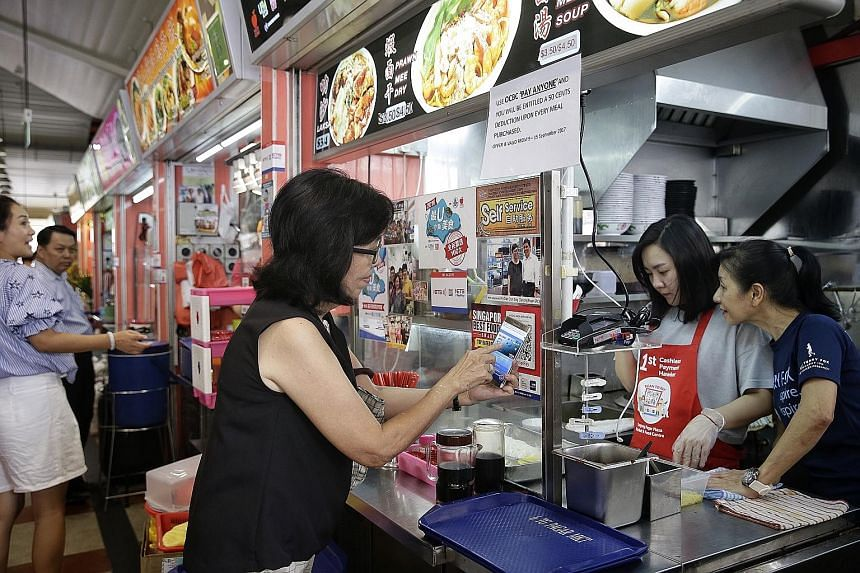 A patron scanning the QR code at Tanjong Pagar Plaza Market and Cooked Food Centre. Hawkers get a confirmation on their terminals - and receive payment the next working day.