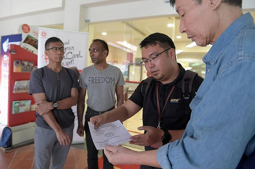 Iscos' social service executive Brian Kang, 27, showing a former inmate how to apply for his SingPass. Looking on are Mr Mohamed Morsidi, 52, and Mr Arulandu-Devasagayan, 47.