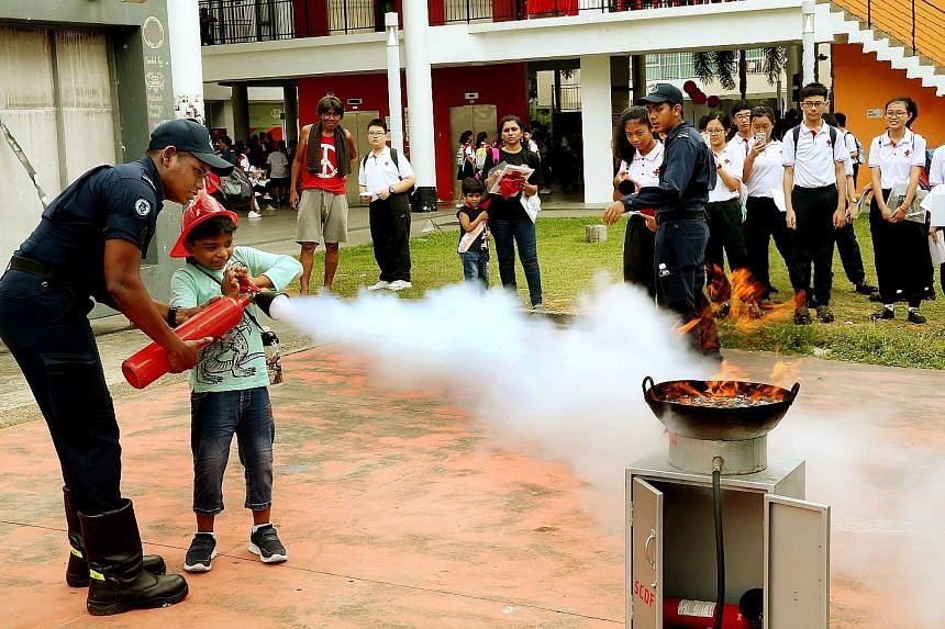 Dinesh Durai Kannan, nine, learning how to use a fire extinguisher at yesterday's event at Taman Jurong Community Club where the Singapore Red Cross was marking World First Aid Day with a carnival.