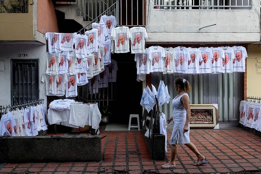 T-shirts featuring Pope Francis on sale in Colombia, ahead of the pontiff's celebration of an open-air mass in Medellin yesterday. Hundreds of thousands were expected to gather to hear the Pope speak. He was also due to visit a home for children who