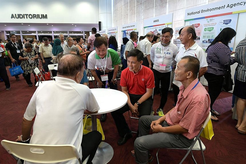 Minister in the Prime Minister's Office Chan Chun Sing and senior volunteer group RSVP Singapore's president Koh Juay Meng (in white and green shirt) chatting with participants at the launch of a scheme yesterday to encourage older workers to become