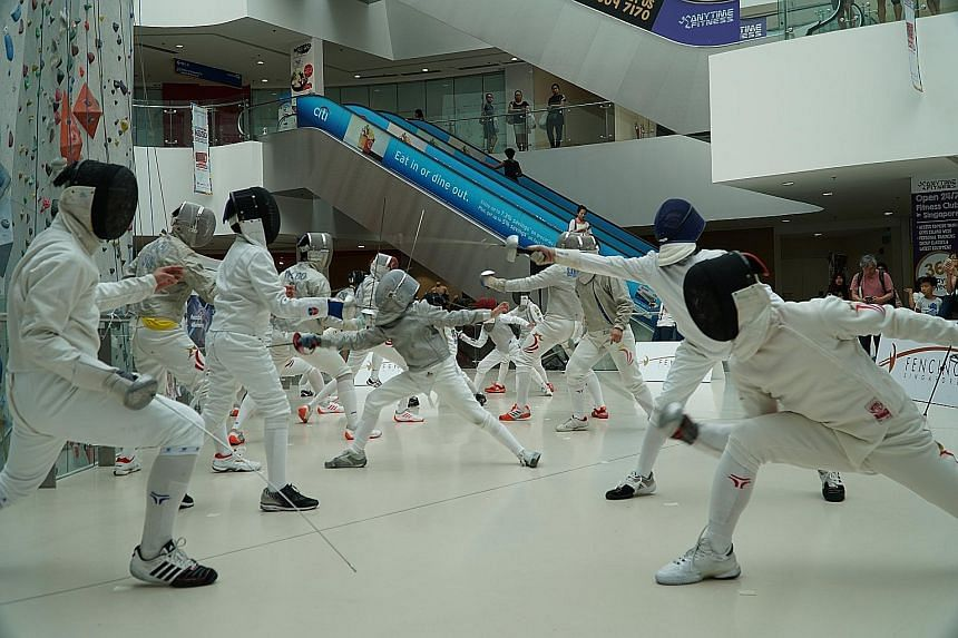 Fencers participating in a flash mob at Kallang Wave Mall yesterday in celebration of World Fencing Day. Earlier, SEA Games champion Lau Ywen and medallists Ahmad Huzaifah Saharudin and Jet Ng also spoke about their journey in the sport.