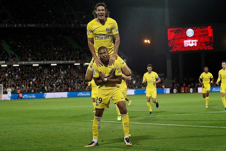 Kylian Mbappe (bottom) celebrates scoring Paris Saint-Germain's second goal with Edinson Cavani. Cavani netted twice as PSG trounced Metz 5-1.