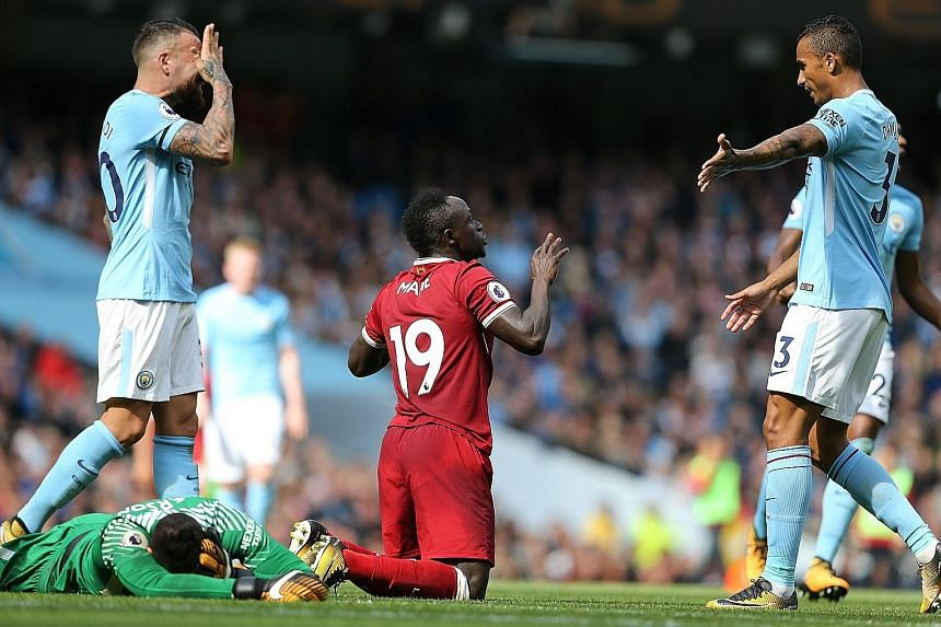 Manchester City's goalkeeper Ederson on the ground after being fouled by Liverpool forward Sadio Mane, resulting in a red card for the Senegal international.