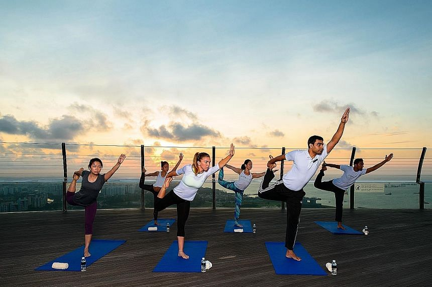 Romanian tennis professional Simona Halep (centre) taking part in a morning yoga session at Marina Bay Sands during a promotional tour of the WTA Finals in 2015.