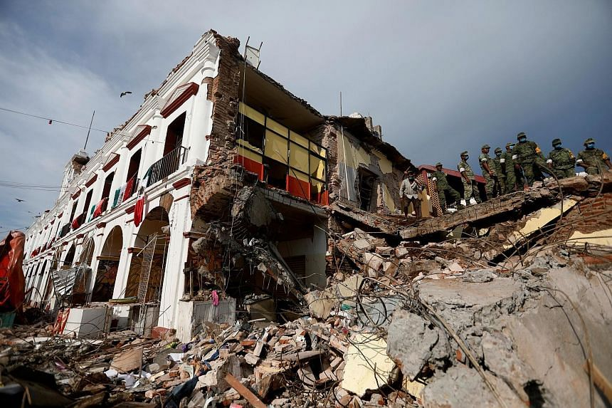 Soldiers at the ruins of a building in Juchitan, in Oaxaca. Mexican President Enrique Pena Nieto toured the hardest-hit city, where at least 36 bodies were pulled from the ruins.