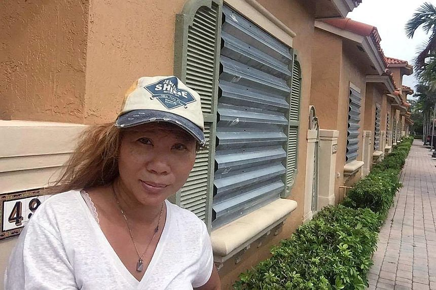 Ms Selina Seet outside her home in Florida. She has gone into lockdown mode, with her windows and patio doors boarded up by hurricane shutters.