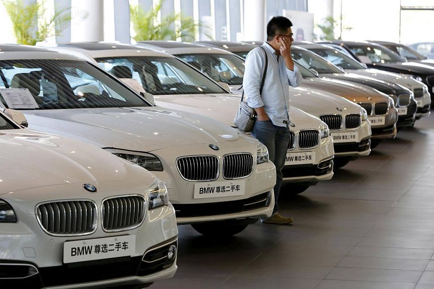A man takes a look at second-hand BMW cars at a dealer shop in Beijing, China.