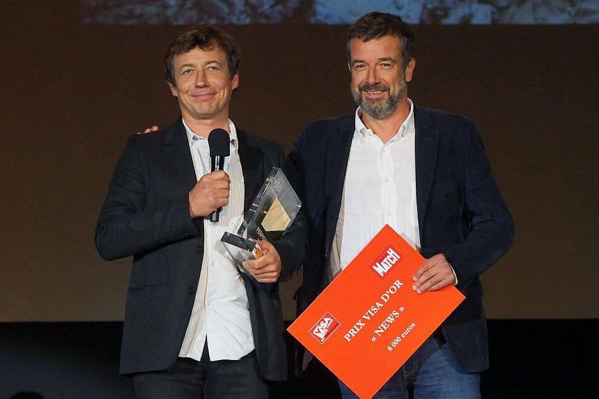 French photographer Laurent Van der Stockt (left) receives the Paris Match Visa d'Or award in the news category from Paris Match deputy director Regis Le Sommier on Sept 9, 2017.