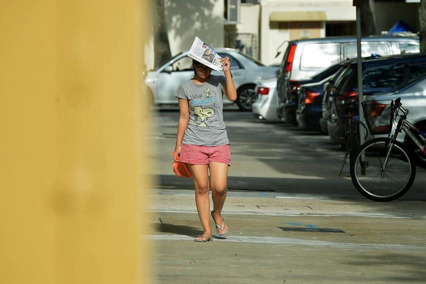 A woman using a newspaper to shade herself from the morning sun and sweltering heat at Yishun.