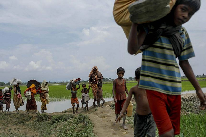 Rohingya refugees arrive from Myanmar through Lomba Beel after crossing the Naf river in the Bangladeshi town of Teknaf on Sept 7, 2017.