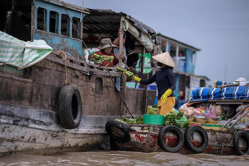 A vendor sells vegetables to a house boat owner in a canal off the Song Hau river at the floating Cai Rang market in Can Tho on July 17, 2017.