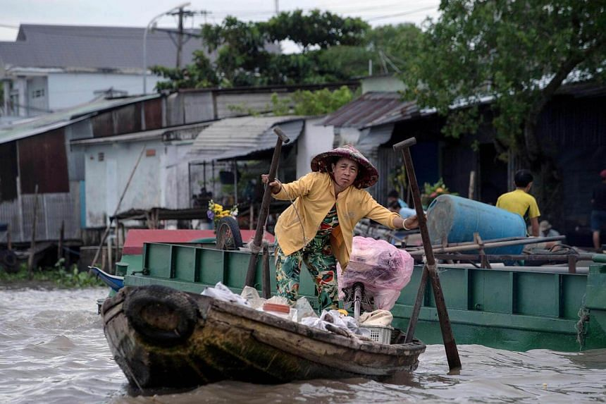 A vendor selling food and drink in search of customers in a canal off the Song Hau river in the floating Cai Rang market in Can Tho on July 17, 2017.