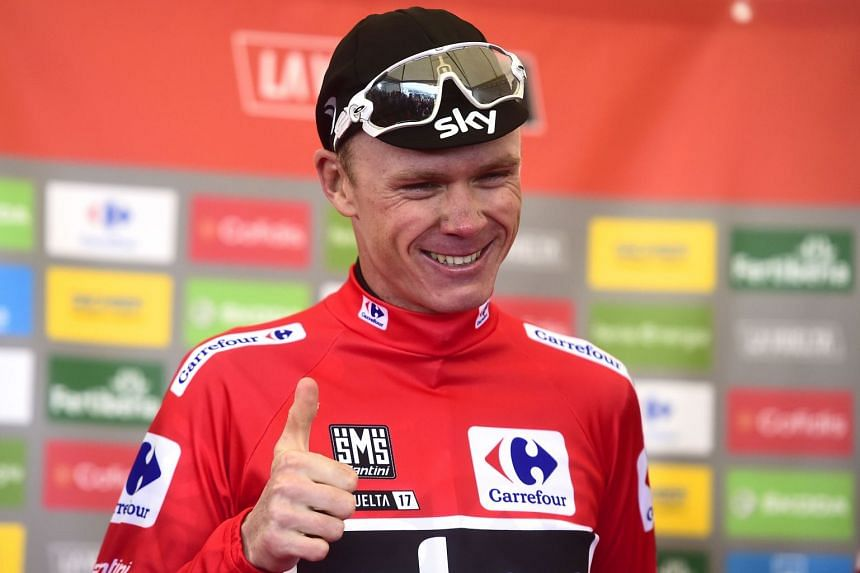 Froome smiles as he sports the overall leader's red jersey on the podium of the 20th stage.