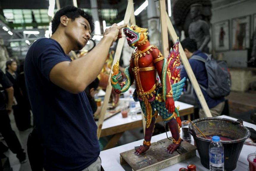 Thai official artists paint deity sculptures which will adorn the elaborate complex of the royal crematorium for late Thai King Bhumibol Adulyadej's funeral ceremony.