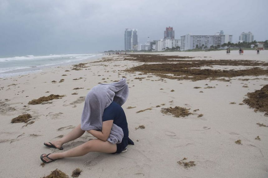 A woman tries to shield herself from flying sand on Miami Beach.