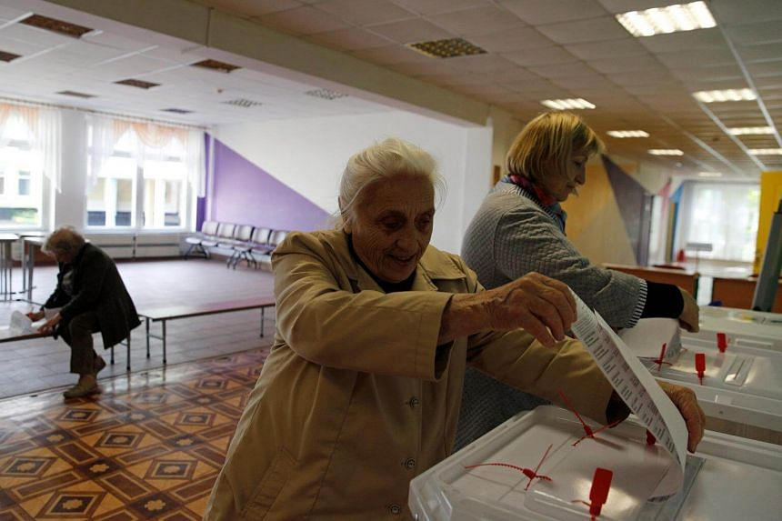 People cast their ballots at a polling station during the municipal election in Moscow, Russia, on Sept 10, 2017.