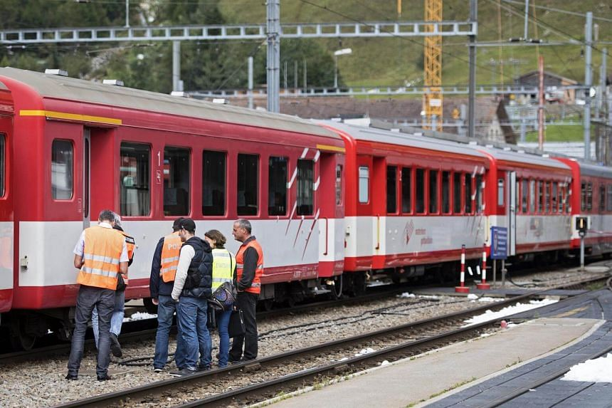 Police staff inspects a crashed train at the Andermatt train station in the Canton of Uri, Switzerland, on Sept 11, 2017.