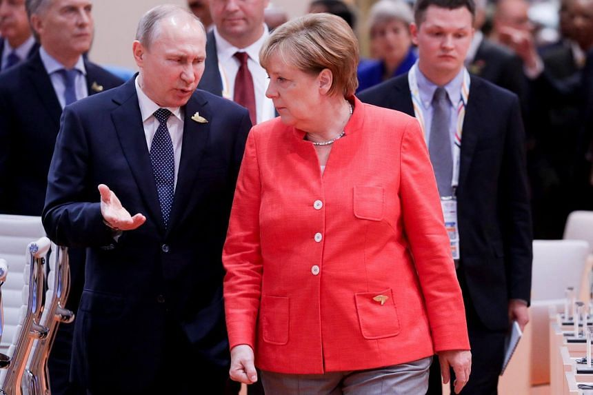 Russia's President Vladimir Putin talks to German Chancellor Angela Merkel before the first working session of the G20 meeting in Hamburg, Germany, on July 7, 2017.