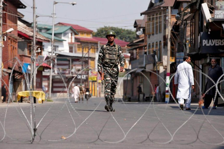 An Indian policeman patrols a deserted street during restrictions a day before the death anniversary of Burhan Wani, a commander of the Hizbul Mujahideen militant group, in downtown Srinagar, on July 7, 2017.