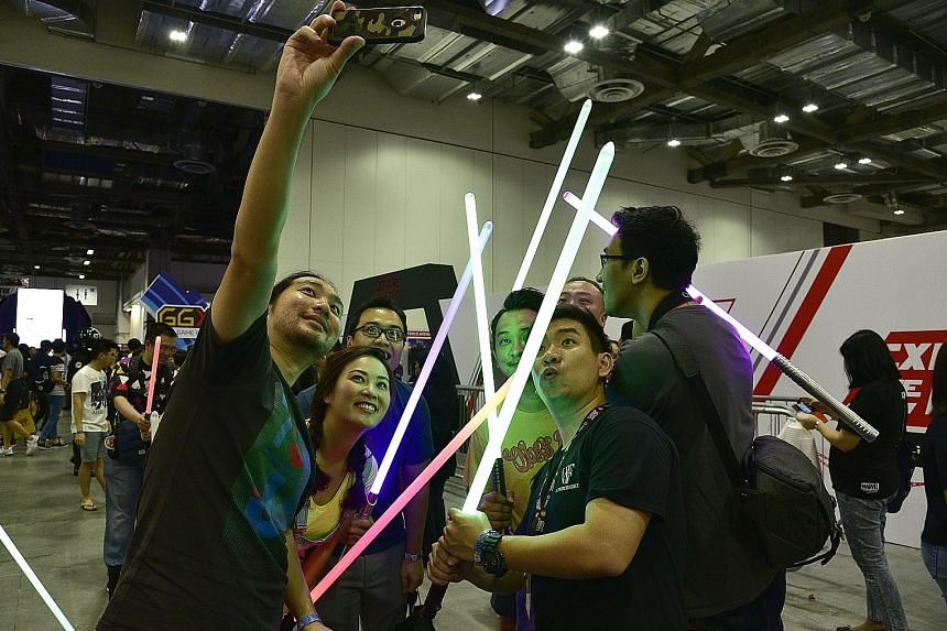Cosplayers came dressed as, among other characters, Spider-Men and Harley Quinn; while other attendees crossed lightsabers for a wefie (above).
