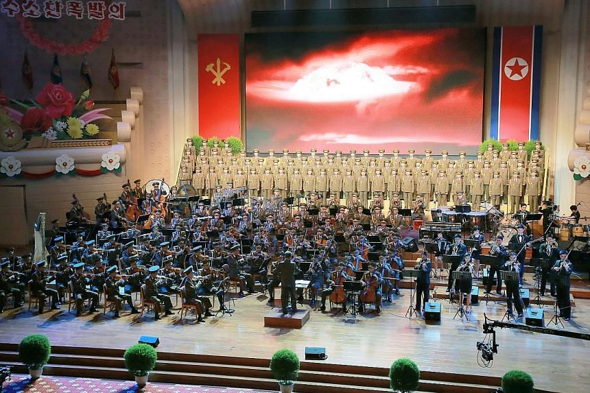 "An orchestra and a choir performing during a celebration for nuclear scientists and technicians who contributed to a hydrogen bomb test. Mr Kim dubbed the latest test the ""great auspicious event of the national history""."