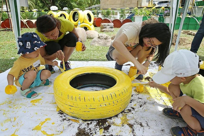 (From far left) Samuel Wong, three, nursery teachers Rauth Gamo, 28, and Woon Tien Li, 31, and Julius Lee, four, paint a tyre bright yellow for their outdoor play space at St James' Church Kindergarten.