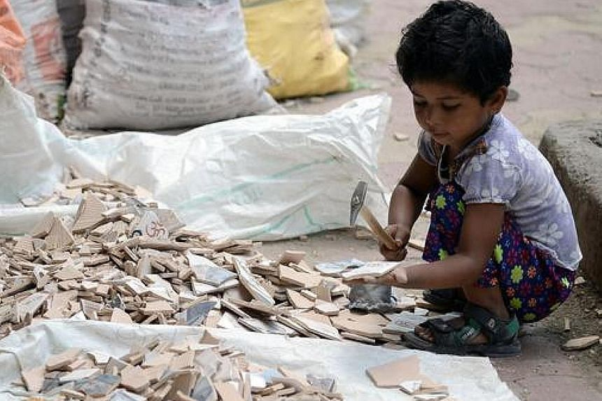 A child breaking tiles outside a construction site in Mumbai in 2015. Nobel Peace Prize winner Kailash Satyarthi and his team raid mills, mines and factories to rescue children from bonded labour.