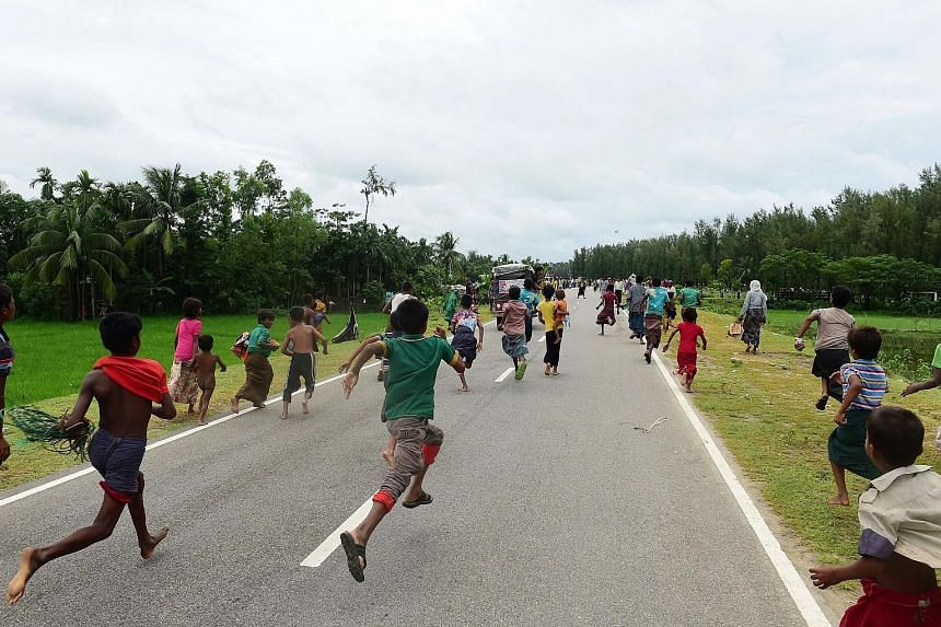 "The children of Rohingya refugees running after a vehicle carrying relief supplies near the Bangladeshi town of Teknaf yesterday. The UN said the wave of hungry and traumatised refugees fleeing Myanmar's northern Rakhine state is ""showing no signs of"