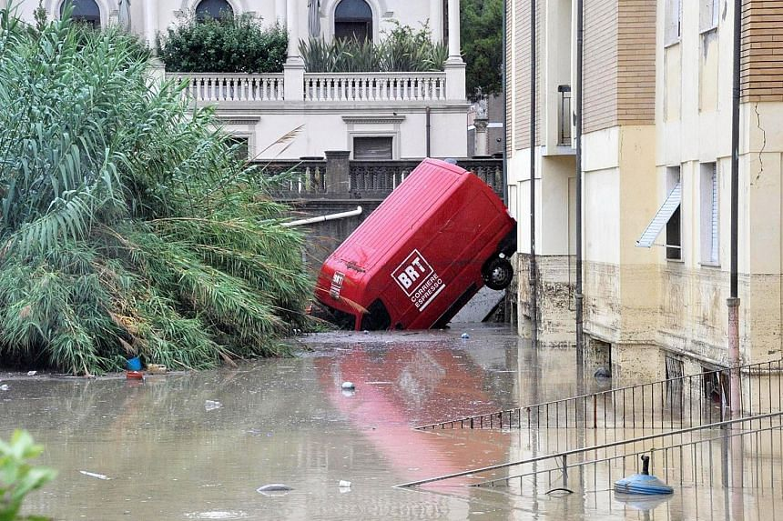 A van stuck in a flooded street in Livorno, Italy, yesterday. Fire services said the city took the brunt of the flooding.