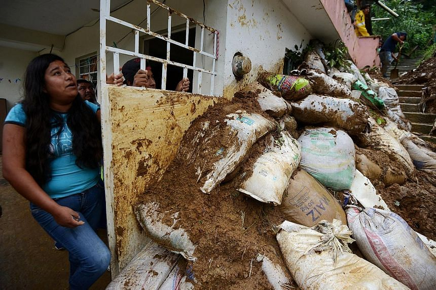 Residents in a neighbourhood struck by mudslides that were set off by heavy rains after storm Katia swept through Xalapa city in Veracruz last Saturday. Two major catastrophes just days apart have left Mexico reeling from the punch.