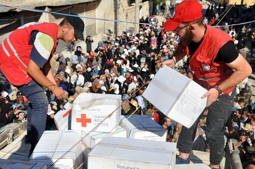 Members of the Syrian Red Crescent distributing aid parcels to Deir Ezzor residents on Saturday. Large crowds gathered to receive bags of rice, bulgur wheat, olive oil and preserves, as well as hygiene products.