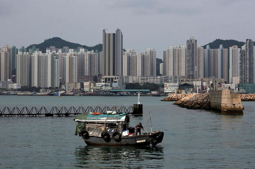 A boat sails in front of private and public housing blocks in Hong Kong, China.