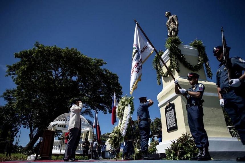 """Ferdinand """"Bongbong"""" Marcos Jnr (left), a former senator and son of the late dictator Ferdinand Marcos, salutes in front of a monument dedicated to his father as he offers a wreath during celebrations to mark his father's 100th birthday in Batac, Ilo"""