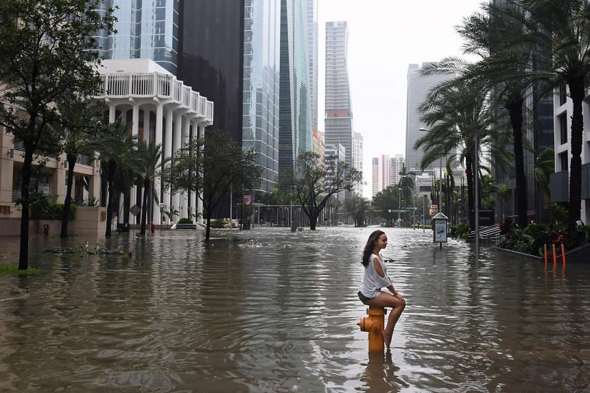 A girl sitting on a fire hydrant on a flooded street as Hurricane Irma hits Miami on Sept 10, 2017.