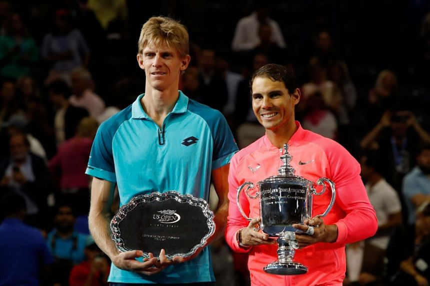 Rafael Nadal (right) of Spain holds the trophy after defeating Kevin Anderson of South Africa.