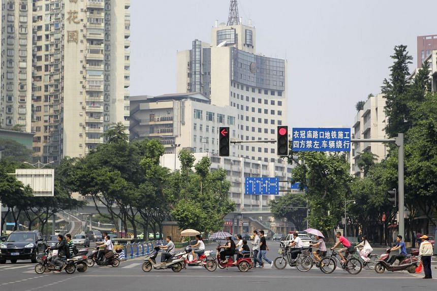 Motorcyclists and cyclists travelling in their dedicated lanes at a traffic junction at Ren Min Nan Road in Chengdu, Sichuan province, on May 17, 2012.