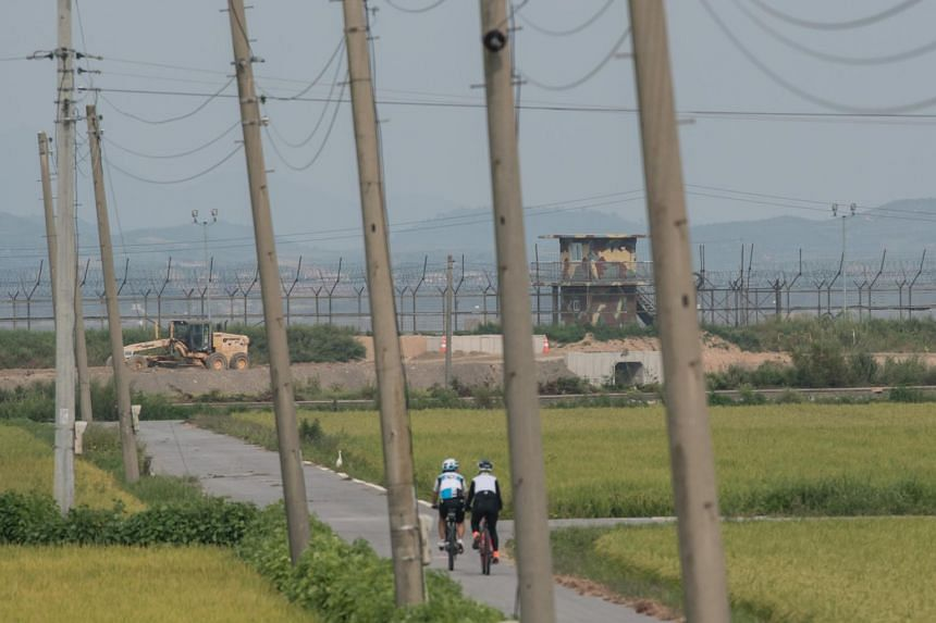 Cyclists pass before a South Korean military guard post before the skyline of North Korea (top) and the barbed-wire fence of the Demilitarized zone (DMZ) separating the two countries, on Ganghwa island on Sept 4, 2017.