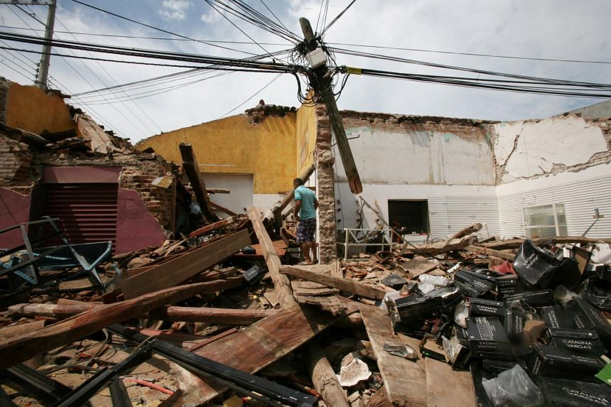 A man walks among the debris of a house destroyed in an earthquake that struck off the southern coast of Mexico, in Juchitan, on Sept 8, 2017.